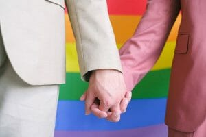 Couple holding hands in front of a gay pride flag